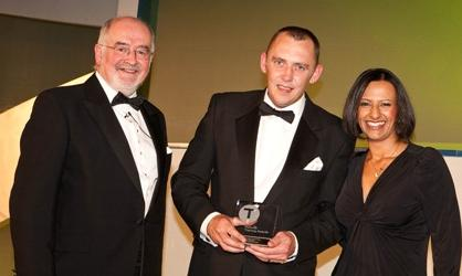 Neil Kershaw receiving award from TV presenter Ranvir Singh