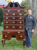 Auctioneer Tim Chapulis stands next to a magnificent 2-piece Queen Anne high boy