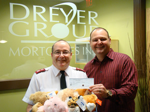The Salvation Army accepting the cheque and some stuffies for kids.