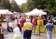 Visitors enjoy the open air country atmosphere at Round Lake Antiques festival.