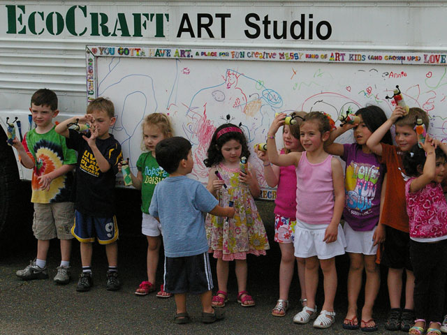 Children displaying their recycled bottle art.