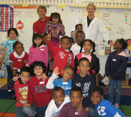 An enthusiastic Kindergarten class posing with two scientist volunteers