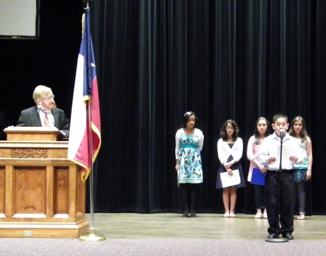 Winning students present their entries as attorney Joseph B. De Mott looks on.