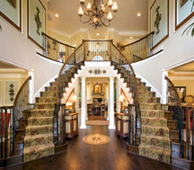The Hampton foyer with dual staircase at Randolph Ridge by Toll Brothers
