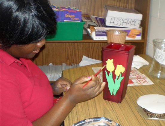 Jessica, a Goodwill L.I.F.E. Academy student, paints a vase for the fundraiser