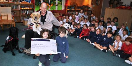 Allen Parton from Hounds for Heroes receives the cheque from Dunannie children