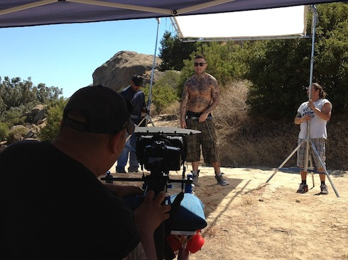 Rapper Suga Shane on set at an outdoor location.