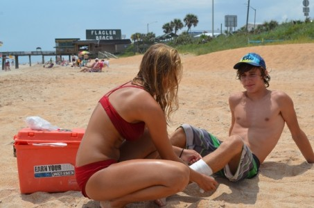 Flagler Beach Lifeguard Stephanie Colasanti wraps Lukas Stocker's, 15, shin.