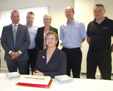 Helen Jones (centre) prepares to cut the cake