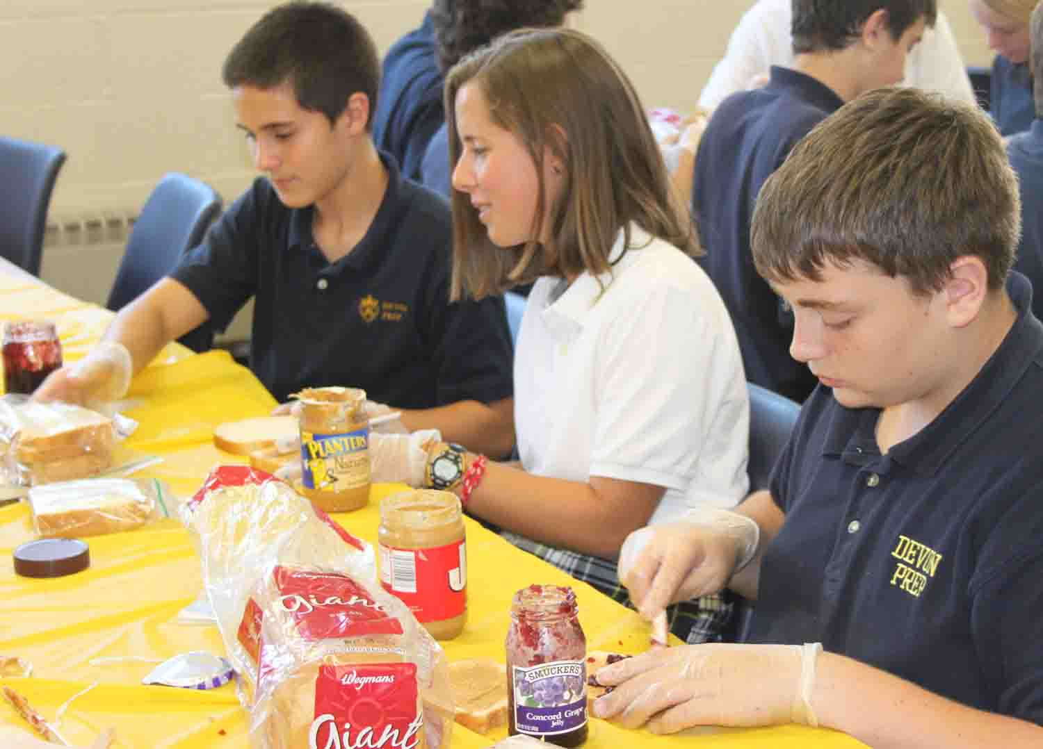 Devon Prep and Notre Dame Freshmen make sandwiches for a food cupboard.