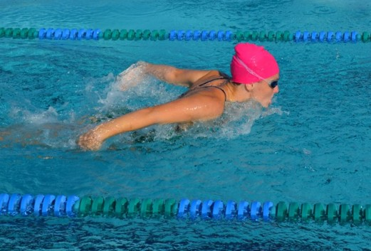 High school swimmers support breast cancer awareness.