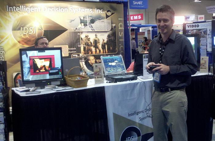 IDSI employees demonstrating the M160 Desktop Trainer at I/ITSEC 2011