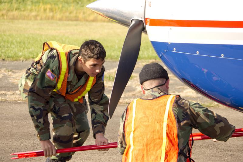 Cadet Airman Noah Stillman & Lt Dale Cates attach a tow bar to move an airplane.