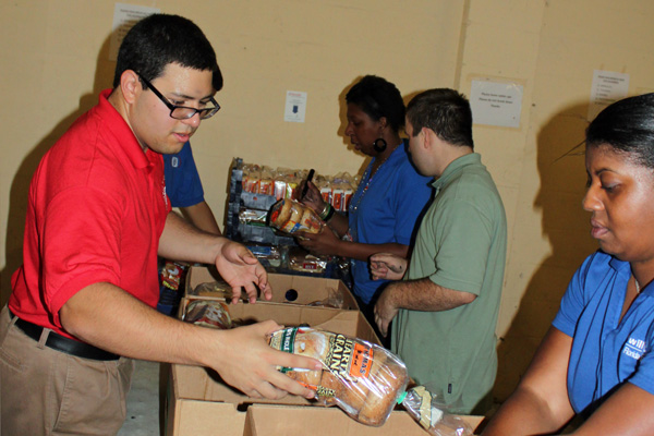 Goodwill L.I.F.E. Academy students and teachers sort bread at the Food Bank.