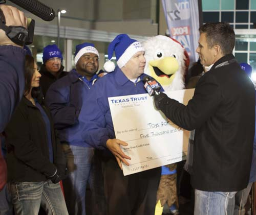 Texas Trust CEO Jim Minge and Fox 4 News as he presented a check for $5,000
