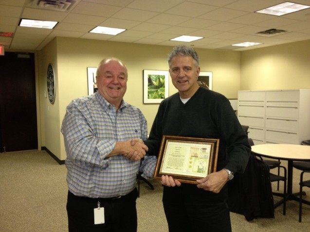 Starbucks Coffee presents UmbrellaOne president, Rick Diamon, with their award.