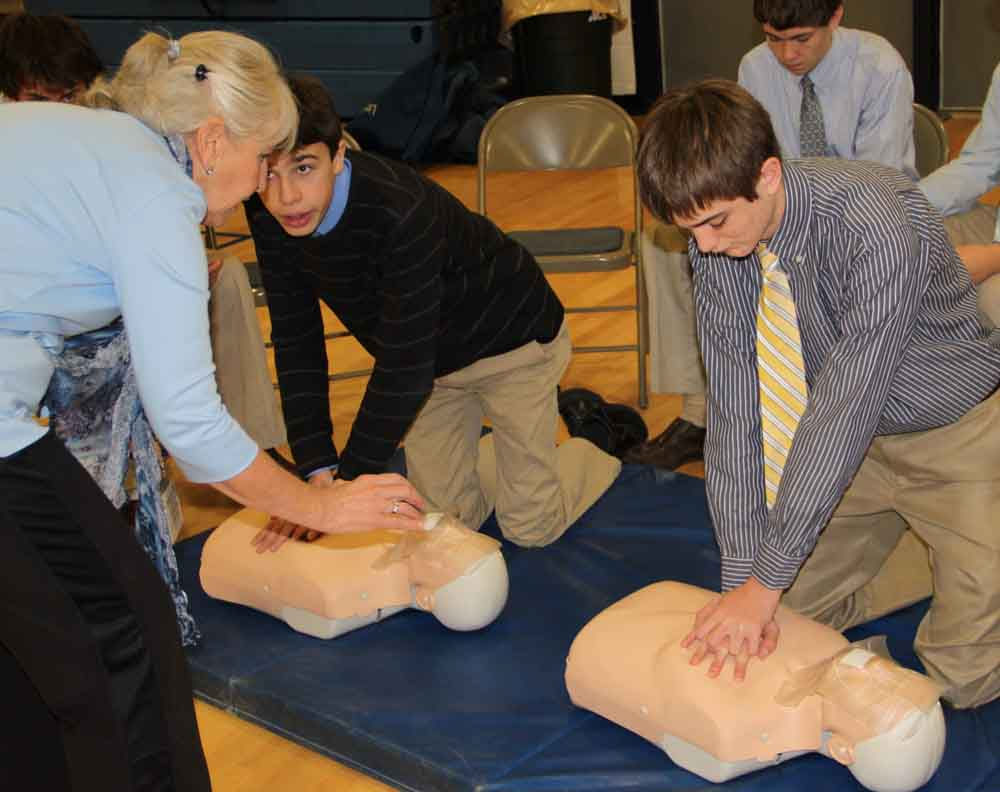 A volunteer Nurse instructs two students on the proper way to perform CPR.