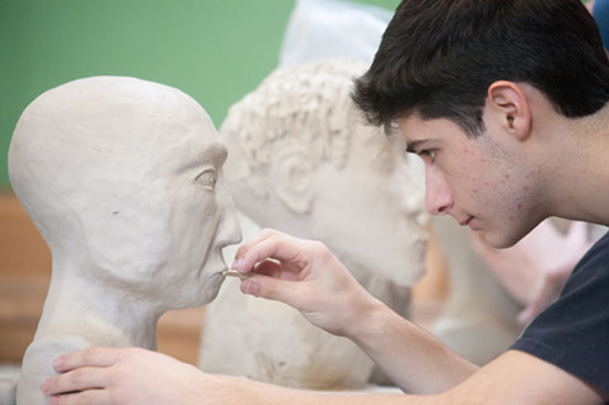 A High School student works on his Clay Portrait.