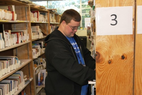 E-Commerce employee, Brady Raulerson, sorting books