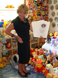 Deb Hoffmann holds her Guinness Book certificates amid her Pooh collection