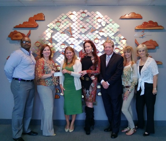 Suzanne Klein presents the $10,000 check to staff at  Children's Home Society