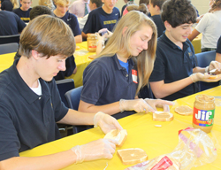 Students make sandwiches for a local emergency food cupboard.