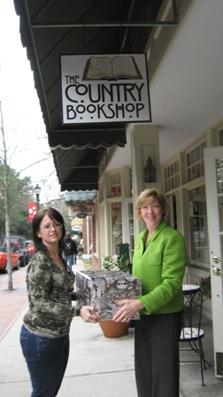 Author Laura Wharton (r) presents Becky Kerr of The Fisher House with books.