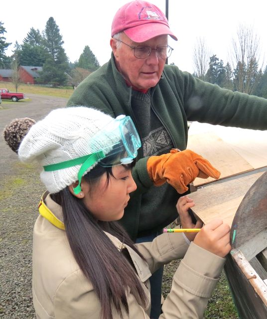 Kerr helping a WSA student in a 2014 Jan Term class on wooden boat restoration