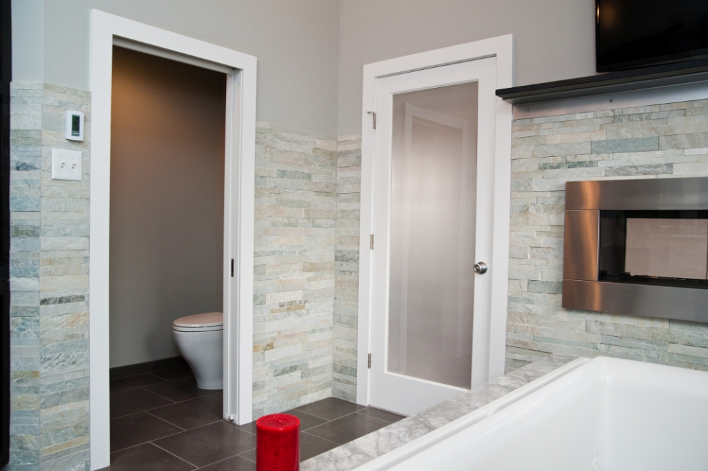 Master bathroom with private water closet and two-sided fireplace
