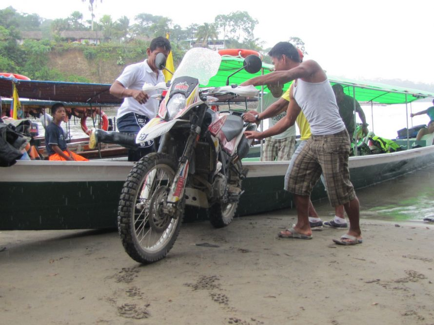 Loading the bikes into the motorized canoe in the Amazon basin