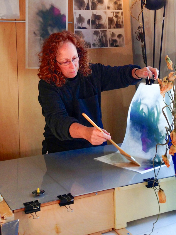 Saunders in her studio creating one of her encaustic art pieces