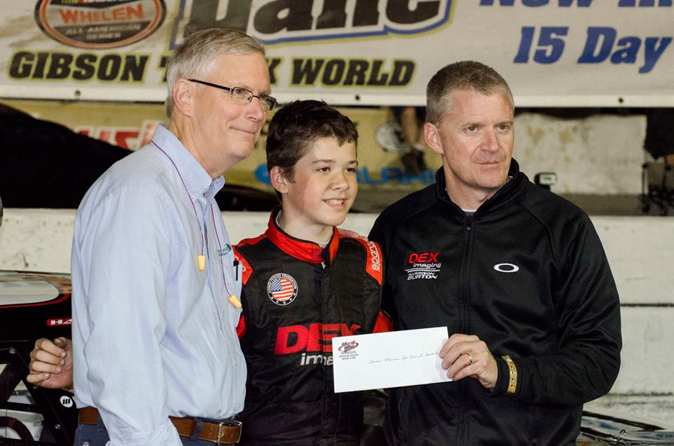 Chet Bell (left), receiving check from Harriston Burton with his dad, Jeff.