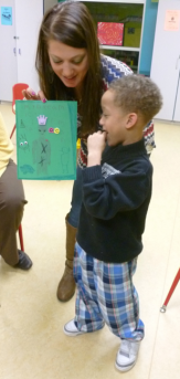 Volunteer helps child with Show And Tell.