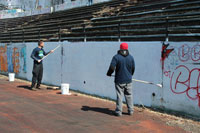 Volunteers paint over graffiti-riddled walls of the historic Hinchcliffe Stadium