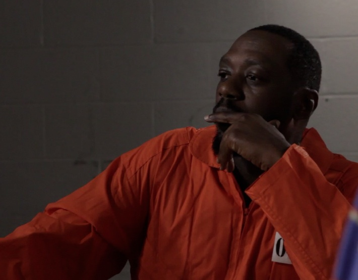 Actor Edwin Lee Gibson as Raqmaan in prison visiting room.
