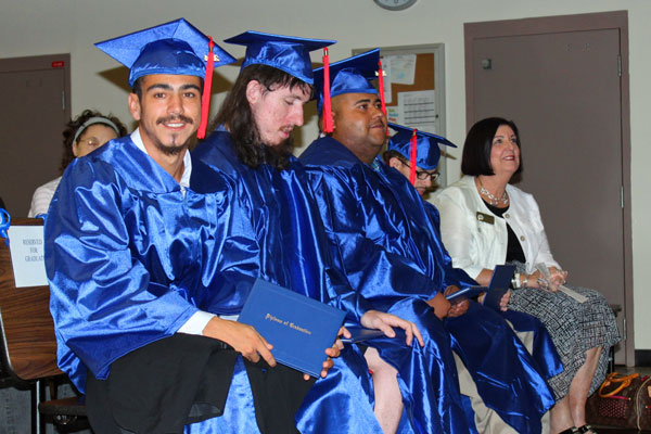 Andrew Cordova smiles alongside fellow graduates and Dr. Nancy Graham