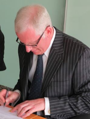 CEO Greg O'Neill signing the formal registration papers