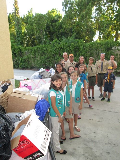 Girl and Boy Scouts pose next to some of their donations during a drop-off
