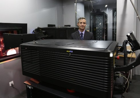 Don Shaw next to Christie Laser Digital Projector