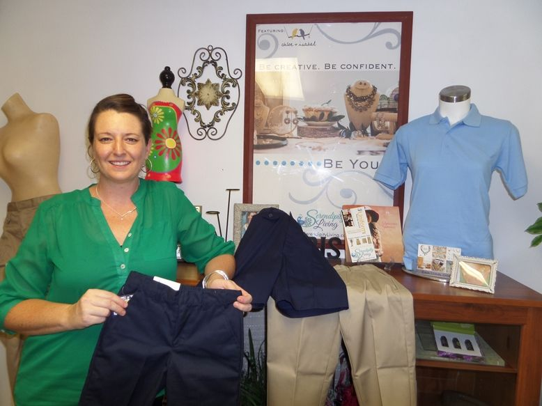 Julia Fuentes with some of her uniforms in her shop in Palm Coast.