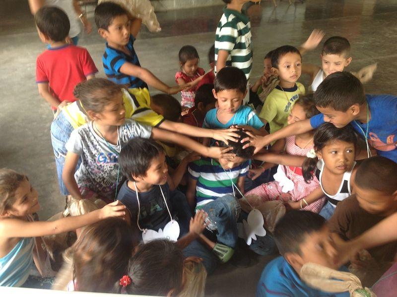 Children Laying Healing Hands on a Child in Honduras.