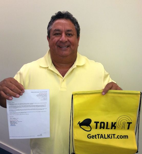 Curtis Ceballos of TALKiT holds up the Innovation Awards Letter he Received.
