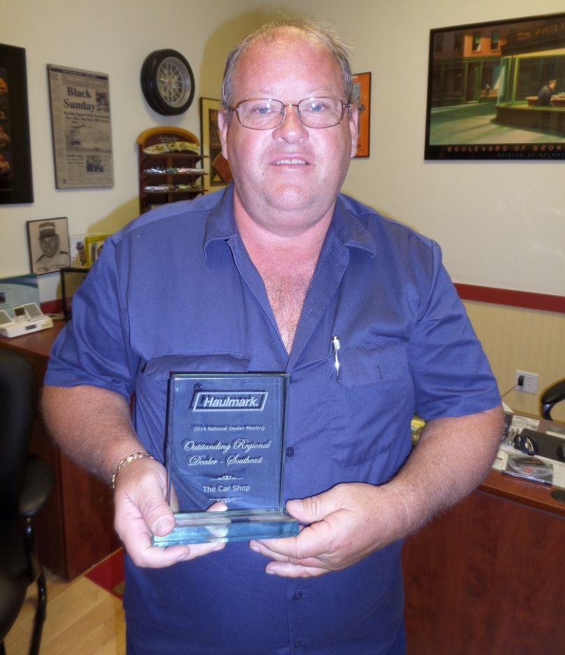 Robin Hanger, owner of Best Price Trailers, with his Top Performance Award.