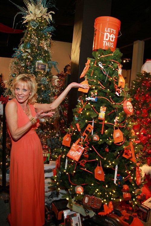 A volunteer at the Festival of Trees shows off the 2013 Home Depot tree