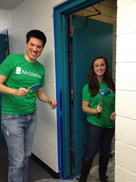 Andrew Collins and Hallie D'Agostino painting a door at the Hillcrest YMCA.