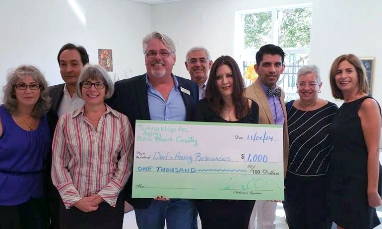 PBC Partnership for Aging presents check to Deaf & Hearing Resources of PBC