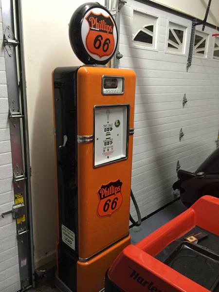 Fully restored Phillips 66 gasoline pump with Harley-Davidson colors.