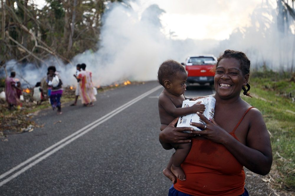 A woman smiles after receiving aid , AP Photo/Nick Perry