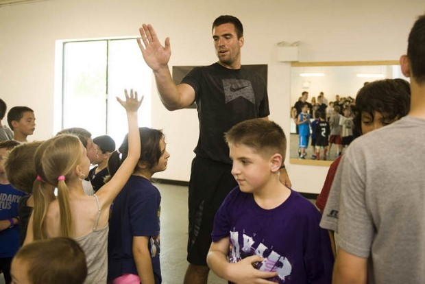 Joe Flacco giving high fives to particpants from the previous charity workout