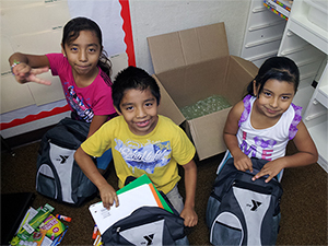 YMCA kids receiving their backpacks, filled with school supplies